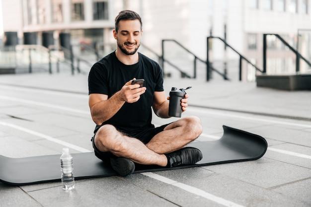 Man rust na buiten training met water en telefoon. gezondheidszorgconcept. sportieve jongeman na het beoefenen van yoga, pauze in het doen van oefeningen, ontspannen op yogamat, sms'en op smartphone.