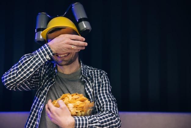 Man rust thuis en kijkt naar tv-shows of sportnieuws op tv-scherm met bierhelm op het hoofd en eet chips