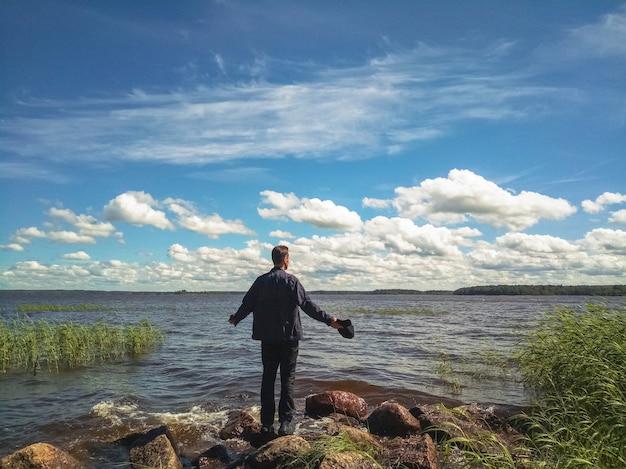Man rusten in de natuur. genieten van het leven. achterkant de man die naar het water kijkt