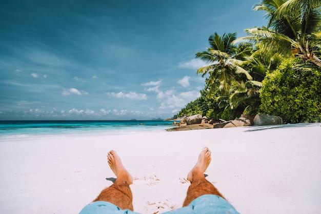 Man rustend op het witte zandstrand met prachtige palmbomen.