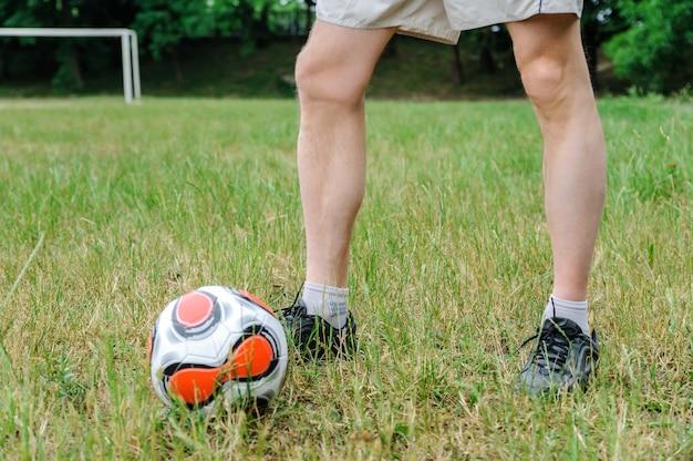 Man's benen op het gras naast voetbal