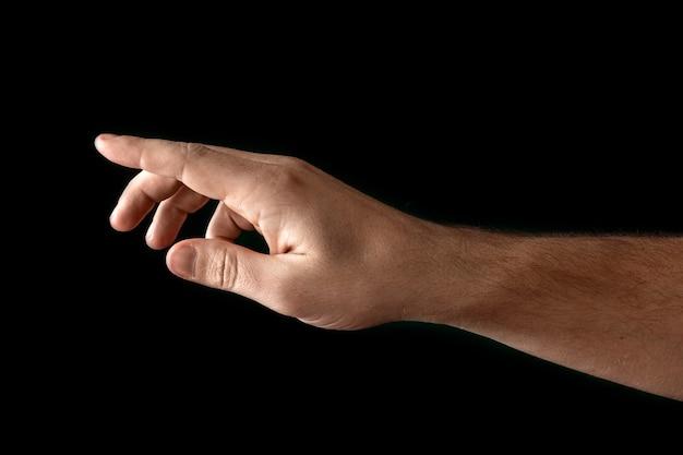 Man's hand aanraken of wijzen op iets geïsoleerd op zwart