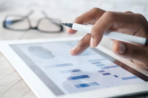 Man's hand bezig met digitale tablet op kantoor, met behulp van zelfgemaakte grafiek