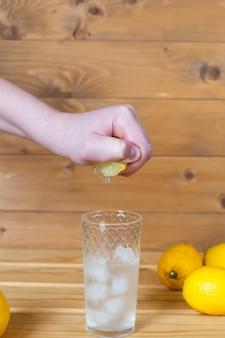 Man's hand die een halve citroen in een kom knijpt.