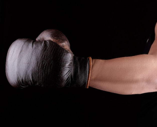 Man's hand draagt een bruine lederen bokshandschoen