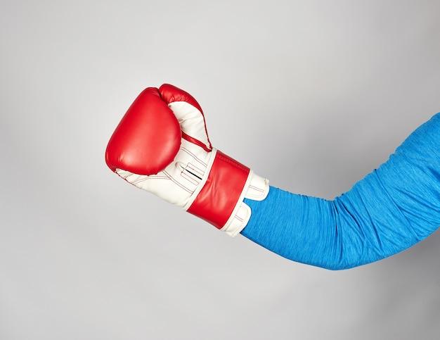 Man's hand draagt een rode lederen bokshandschoen
