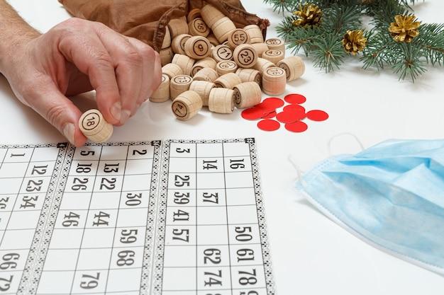 Man's hand met een vat voor een spel in lotto. houten lottovaten met een zak, spelkaarten, rode fiches en een beschermend masker, kerstsparrentakken op de achtergrond. bordspel lotto