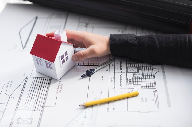 Man's hand met huis-model op blauwdruk op kantoor