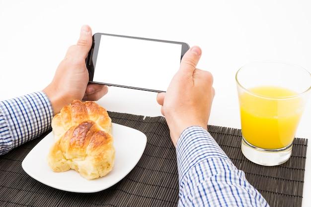 Man's hand met mobiele telefoon met leeg wit scherm bij het ontbijt