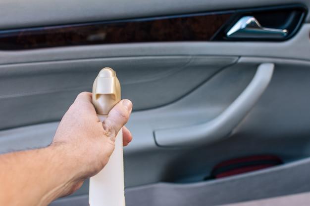 Man's hand met reinigingsspray om de auto schoon te maken.