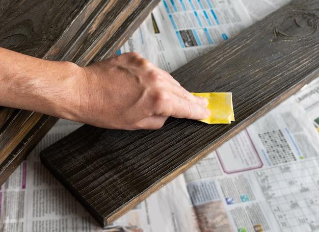 Man's hand met schuurpapier poetsmiddelen geverfd bord, handmatige houtbehandeling
