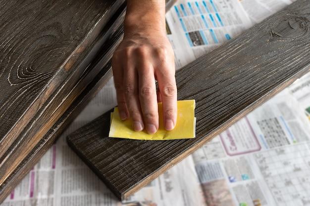 Man's hand met schuurpapier poetsmiddelen geverfd bord, houtbehandeling