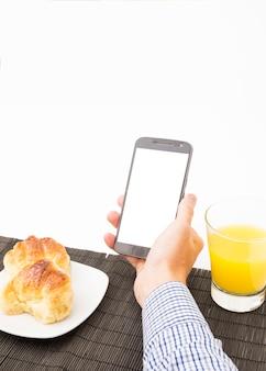 Man's hand met smartphone met leeg scherm bij het ontbijt