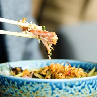 Man's hand met stokjes over een bord met japanse, thaise, chinese maaltijd - rijst, champignons, groenten.