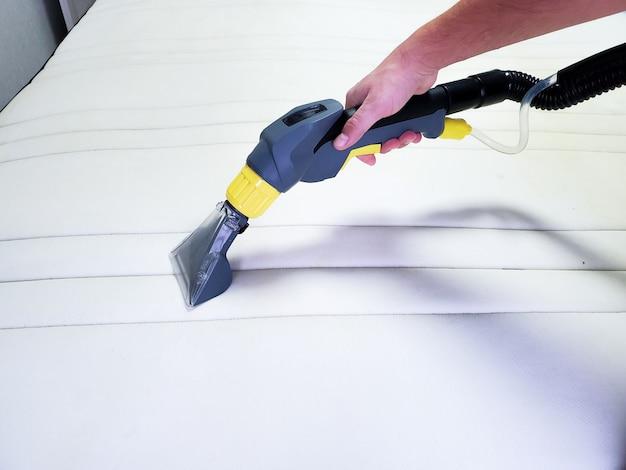 Man's hand reinigt een moderne witte matras met een professioneel schoonmaakmiddel