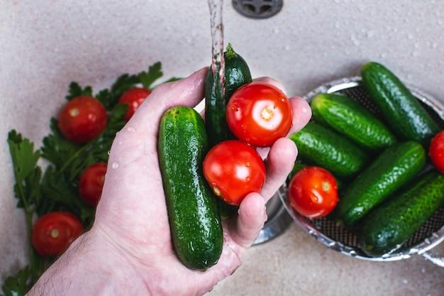 Man's hand wassen van verse komkommers en tomaten