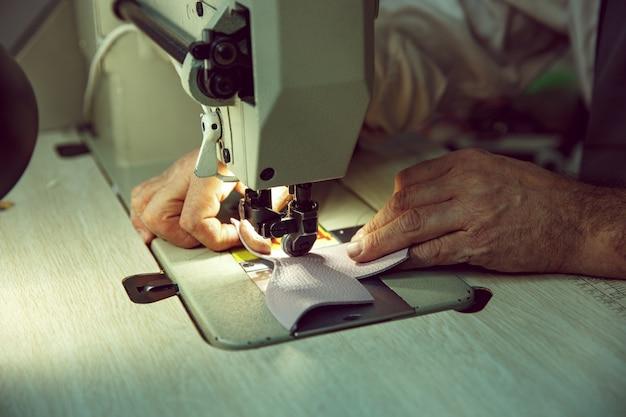 Man's handen achter het naaien. leerwerkplaats. textiel vintage industrieel. de man in vrouwelijk beroep. gendergelijkheid concept