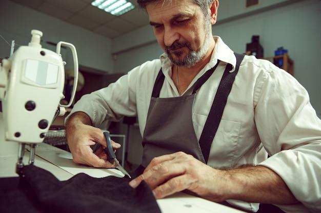 Man's handen en naaimachine. leerwerkplaats. textiel vintage industrieel. de man in vrouwelijk beroep. gendergelijkheid concept
