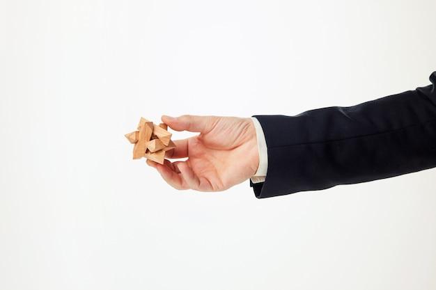 Man's handen met houten puzzel.