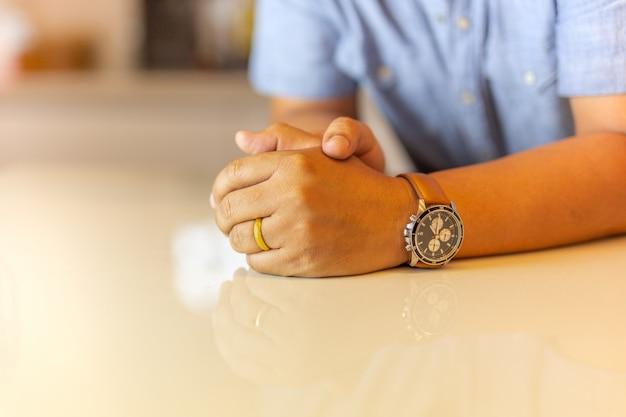 Man's linkerhand met gouden trouwring op zijn vinger op marmeren tafel.