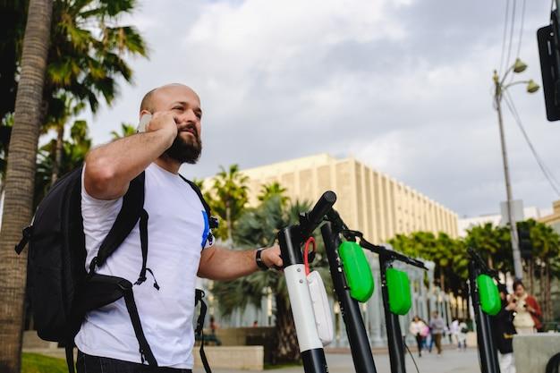 Man scannen qr-code met zijn telefoon voor elektrische scooter huren