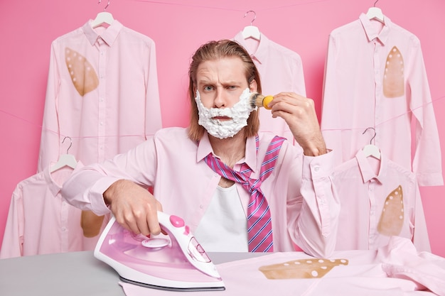 Man scheert baard kijkt met ontevreden uitdrukking draagt overhemd en stropdas om nek gebruikt stoomstrijkijzer om kleding te strelen staat bij strijkplank