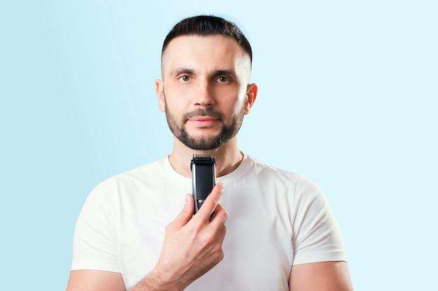 Man scheert zijn baard met een trimeer op blauw