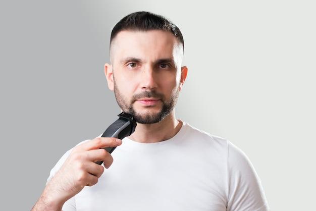 Man scheert zijn baard met een trimeer