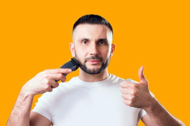 Man scheert zijn baard met een trimmer op geel
