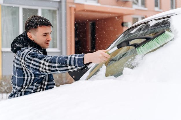 Man schept en verwijdert sneeuw uit zijn auto tijdens een sneeuwstorm. kaukasisch mannetje dat met een speciale borstel staat en sneeuw uit het raam verwijdert