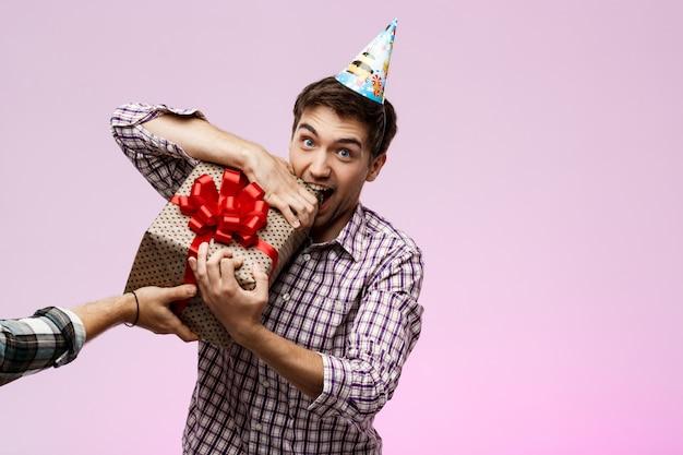 Man scheurt verjaardagscadeau in doos over paarse muur.