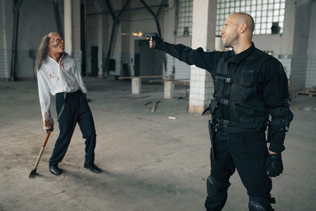 Man schiet zombie, nachtmerrie in verlaten fabriek, kogeleffect. horror in de stad, griezelige beestjes, doomsday apocalyps, bloody evil monster