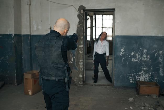 Man schiet zombie, nachtmerrie in verlaten fabriek, kogeleffect. horror in de stad, griezelige beestjes, doomsday apocalyps