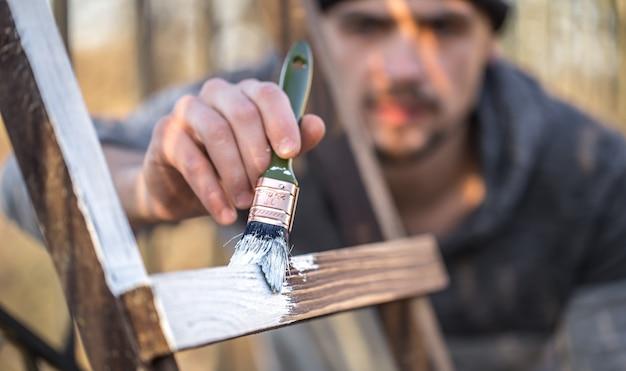 Man schildert met witte verf op houten planken