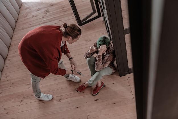 Man schreeuwen. groenharige vrouw zittend op de vloer en agressieve blondharige man die tegen haar schreeuwt