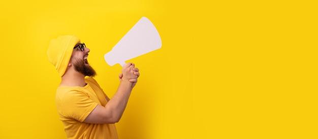 Man schreeuwen in megafoon over gele achtergrond, panoramische lay-out