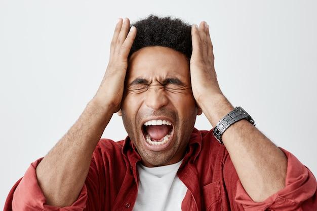 Man schreeuwen van migraine. sluit omhoog portret van zwart-gezondigde ongelukkige kerel met afrokapsel in witte t-shirt onder rood toevallig overhemd die hoofd met handen van hoofdpijn drukken.