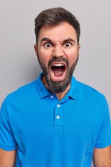 Man schreeuwt boos houdt mond wijd geopend drukt negatieve emoties uit schreeuwt woedend draagt casual blauw t-shirt geïsoleerd op grijs
