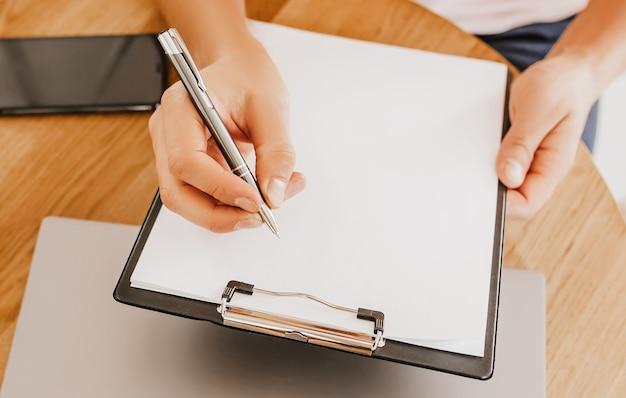 Man schrijft bedrijfsinformatie in notitieblok op werkplek op kantoor met laptop