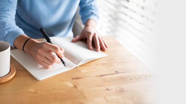 Man schrijft in een dagboek terwijl hij thuis is in het nieuwe normaal
