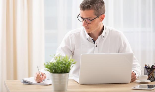 Man schrijft in zijn notitieblok met een notitieboekje geopend op zijn bureau voor hem.