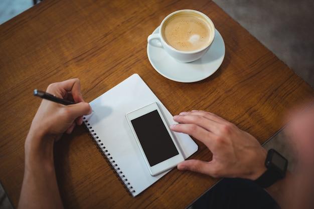 Man schrijft op blocnote terwijl het gebruik van mobiele telefoon