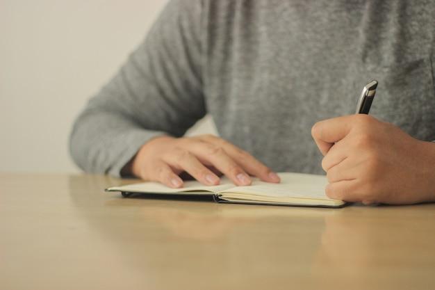 Man schrijft op zijn notitieblok met een zwarte pen
