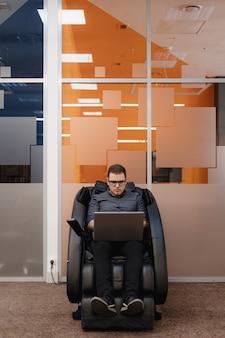 Man schrijven code zittend in fauteuil in het kantoor