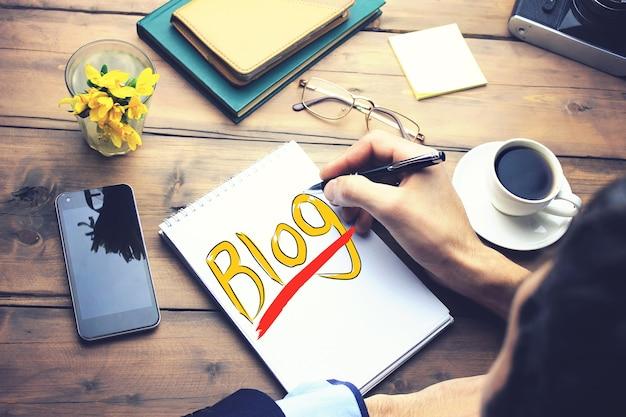 Man schrijven op blog op papier op houten werktafel
