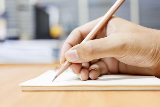 Man schrijven van de notitie met potlood op papier