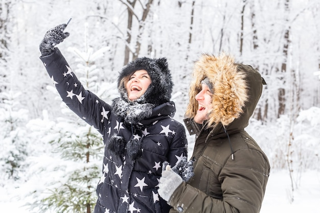 Man selfie foto jonge romantische paar glimlach sneeuw bos buiten winter.