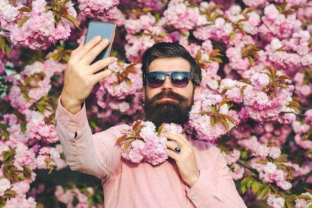 Man selfie maken met mobiele telefoon. lentedag. lente roze sakura bloesem. lente roze bloesem. bebaarde man draagt roze shirt.