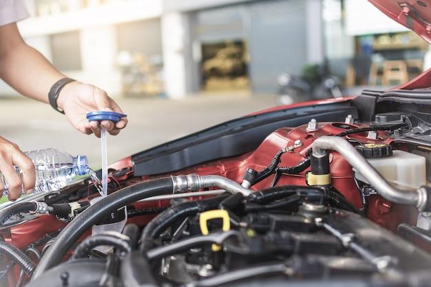 Man service monteur onderhoud inspectie service onderhoud auto controleer motor met vulwater voeg water toe aan de ruitenwisserwagen in garage showroom dealer