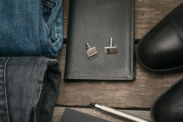 Man set voor de dag van portemonnee, jeans en manchetknopen op een houten bord.